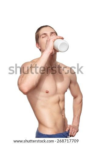 Handsome young muscular athlete drinking with bottle of milk.