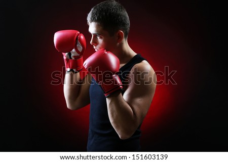 Handsome young muscular boxer on dark background - stock photo
