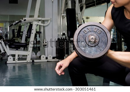 Handsome young muscular sportsman execute exercise with dumbbell - stock photo