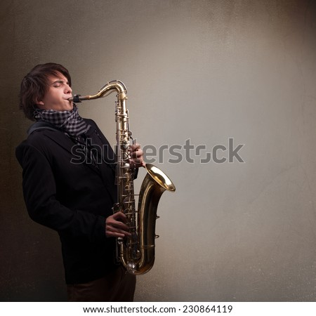 Handsome young musician playing on saxophone - stock photo