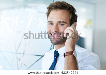 Handsome young office employee smiling warmly at the camera while using his mobile phone in a bright modern workplace
