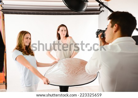 handsome young photographer taking pictures of a beautiful girl  fashion model - stock photo