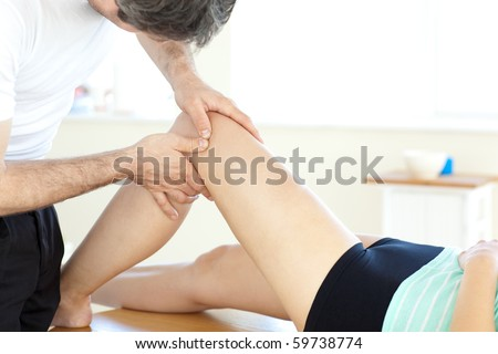 Handsome young physical therapist giving a leg massage in a health center - stock photo