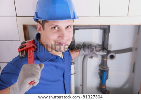 Handsome young plumber with a wrench
