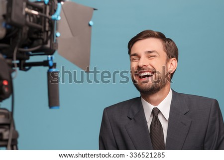 Handsome young reporter is standing and making his report. He is looking at the camera and laughing. Isolated on blue background - stock photo