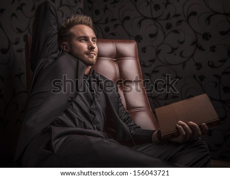 Handsome young serious man in dark suit with book relaxing on luxury sofa.  - stock photo