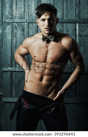 Handsome young sexy man brunet with naked muscular athletictorso dark bow tie on neck waering black underwear and unbutton trousers looking straight posing on gray wooden background, vertical photo - stock photo