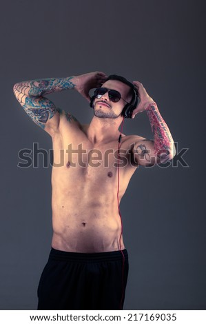 handsome young shirtless latin tattooed man holding headphones on his head posing - stock photo