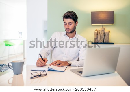 Handsome young smiling businessman working from home with a laptop with his coffee mug - stock photo