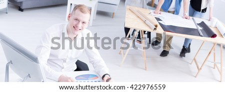 Handsome young smiling man sitting in a spacious office in company running by young people. In the background young architects doing a project