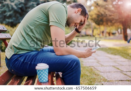Handsome young smiling man sitting on the park bench, drinking coffee and using mobile phone. Lifestyle concept