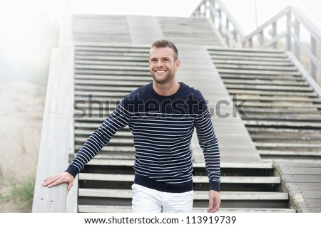 Handsome young smiling man walking down stairs outdoors. - stock photo