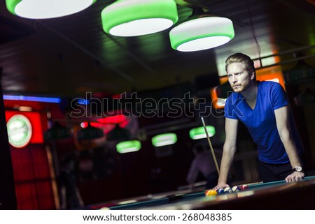 Handsome young snooker player bending over the table in a bar with beautiful ambient lighting - stock photo