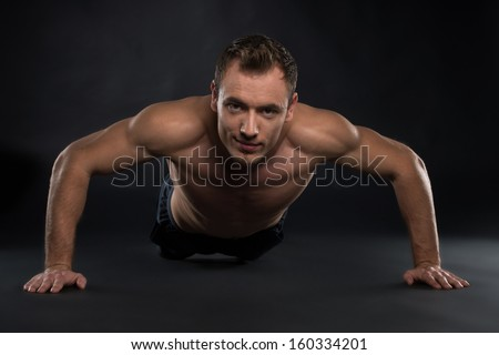 Handsome Young sport man. Fitness muscle model guy making push ups exercise over black background - stock photo