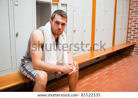 Handsome young sports student sitting on a bench with a towel - stock photo