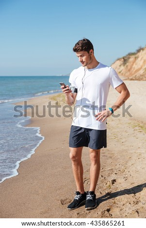 Handsome young sportsman listening to music using cell phone and earphones on the beach - stock photo