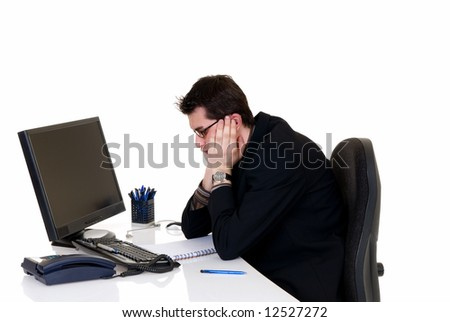 Handsome young stressed businessman at his desk in office, white background,  studio shot.