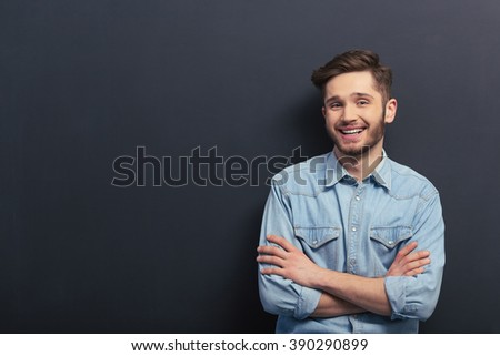 Handsome young student in jeans shirt is looking at camera and smiling, standing with crossed arms against blackboard - stock photo