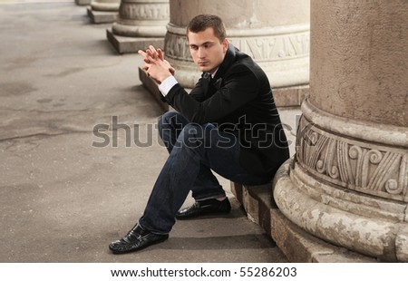 handsome young student sitting near university - stock photo