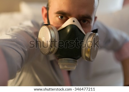 Handsome young stylish caucasian man in respirator on the bed in the bedroom