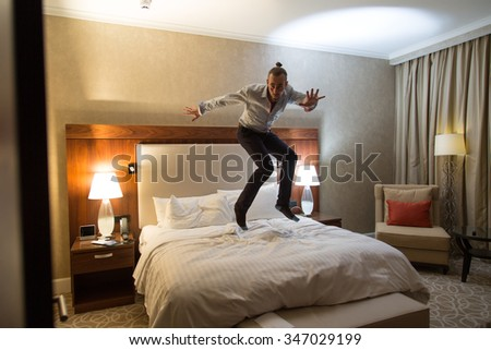 Handsome young stylish caucasian man jumping on the bed in the bedroom