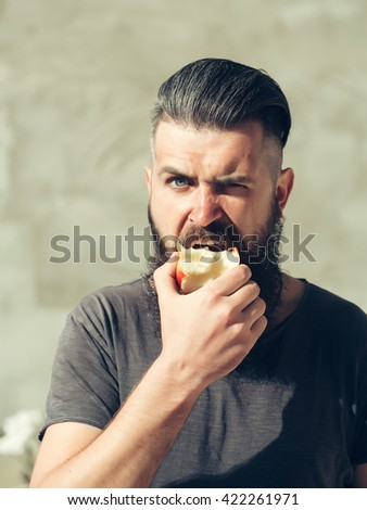 Handsome young stylish hipster man with long beard in grey shirt eating apple outdoor with brunette hair