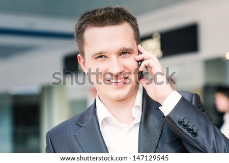 Handsome young successful businessman talking on his mobile - stock photo