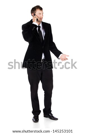Handsome young successful caucasian businessman wearing a formal black suit, tie and white shirt. The man is speaking on his mobile phone.