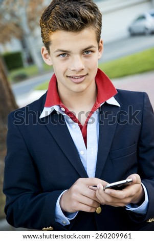 Handsome young teen boy, dressed up and using a cell phone - stock photo