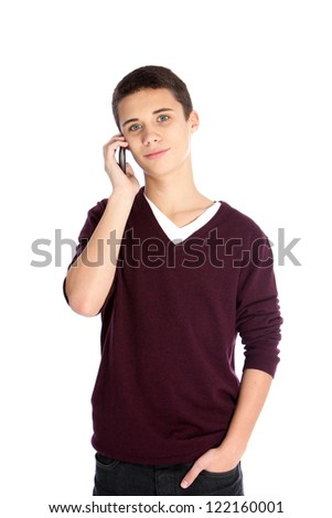 Handsome young teenage boy using a mobile phone standing waiting patiently for his call to be answered or listening to someone speaking at the other end, isolated on white