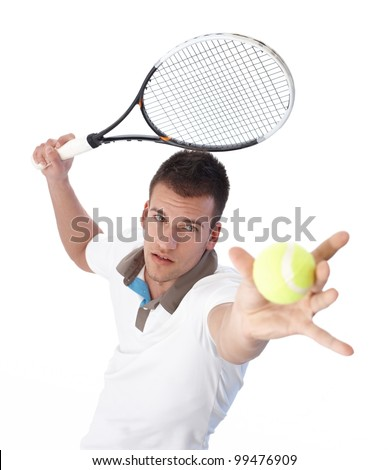 Handsome young tennis player serving, concentrating. - stock photo