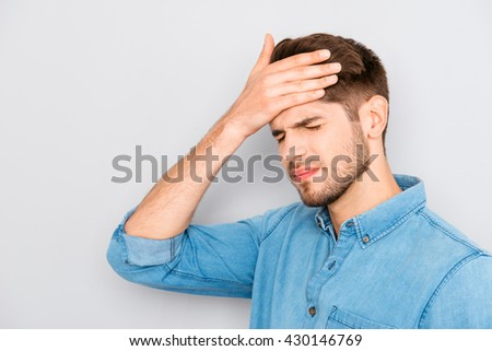 Handsome young tired man with migraine touching head - stock photo