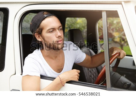 Handsome young unshaven man wearing casual t-shirt and baseball cap backwards looking out of open window of his four-wheel drive vehicle, going on safari trip, planning to spend weekend in wild nature