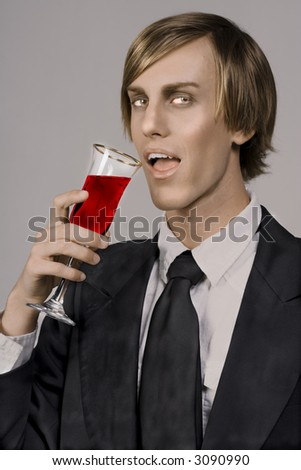 handsome young vampire drinking form Champagne glass (focus on glass) - stock photo