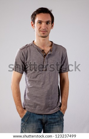 Handsome young white man standing casually and looking at the camera with a happy, playful smile
