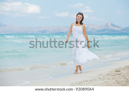 Handsome young woman walking near blue sea.
