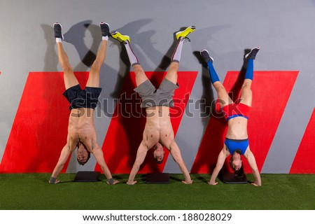 Handstand push-up group pushups workout top position at gym - stock photo