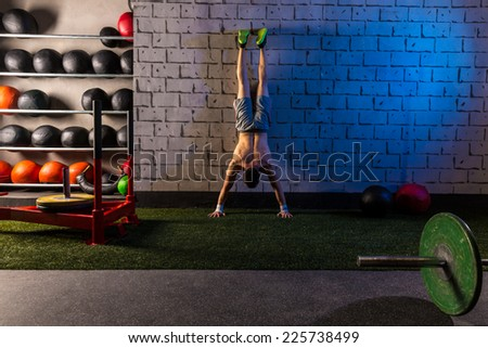 Handstand push-up man workout at gym push ups - stock photo