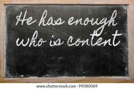 handwriting blackboard writings - He has enough who is content - stock photo