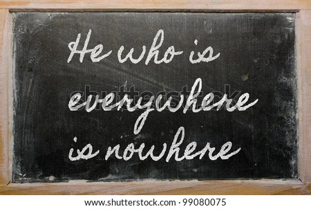 handwriting blackboard writings - He who is everywhere is nowhere - stock photo
