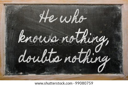 handwriting blackboard writings - He who knows nothing, doubts nothing - stock photo