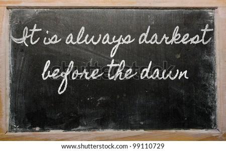 handwriting blackboard writings - It is always darkest before the dawn - stock photo
