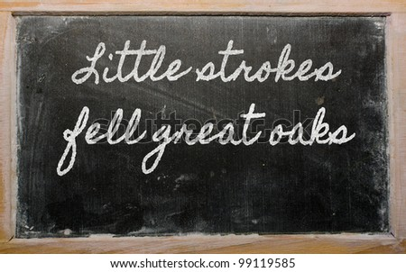 handwriting blackboard writings - Little strokes fell great oaks - stock photo