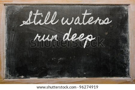 handwriting blackboard writings - Still waters run deep - stock photo