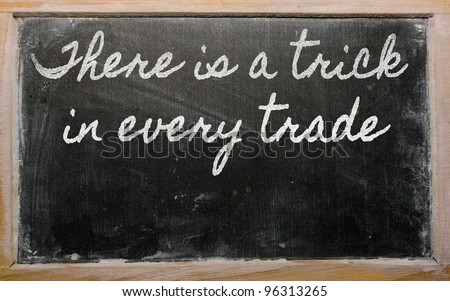 handwriting blackboard writings - There is a trick in every trade - stock photo