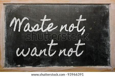 handwriting blackboard writings - Waste not, want not - stock photo