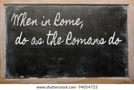 handwriting blackboard writings - When in Rome, do as the Romans do - stock photo
