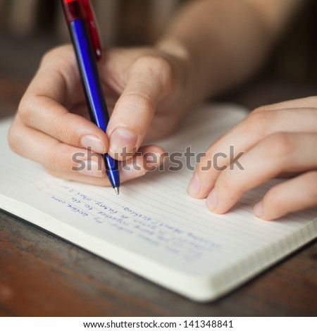 handwriting, hand writes a pen in a notebook - stock photo