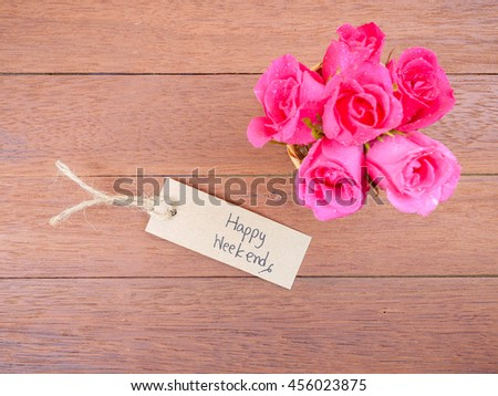 Handwriting Happy Weekend on brown label and bouquet of pink rose flower on wood background with top view - stock photo