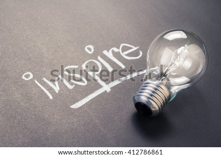 Handwriting of inspire word with glowing light bulb - stock photo